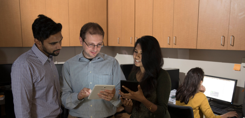 Graduate student Phani Vadrevu, professor Roberto Perdisci and graduate student Karthika Subramani review data on a tablet device while graduate student Roxana Attar works in the laboratory